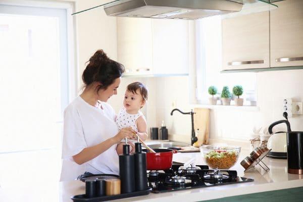 赤ちゃんを抱っこしながら料理をするお母さん