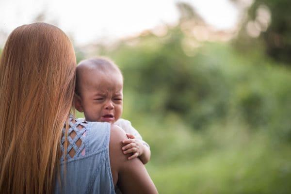 泣く赤ちゃんをあやすお母さん