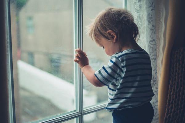 窓際に立つ赤ちゃん
